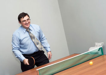 Man plays ping pong in suit