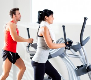 man and woman on elliptical machines