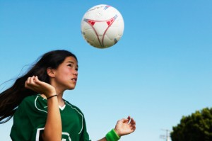 Girl hits soccer ball with head