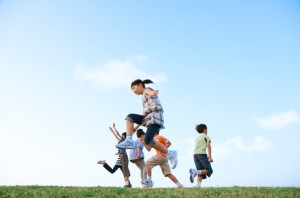 Children jumping and running in open field