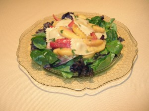 Peach salad with pasta on a plate with greens