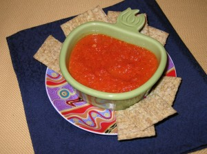 A bowl of red pepper dip on a plate surrounded by homemade pita chips