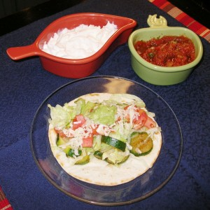 Zucchini burrito on a plate, pictured with salsa and sour cream