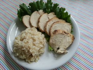 Sliced chicked with scoop of brown rice on a plate with a garnish