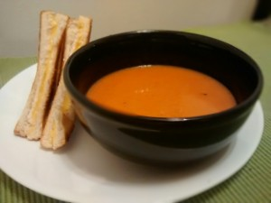 Tomato bisque in bowl with half-sandwich on plate