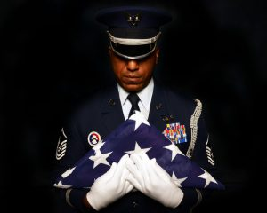 U.S Military Service Member Reverently Holding the American Flag